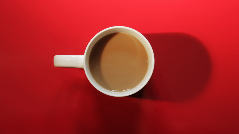coffee filled mug on red background