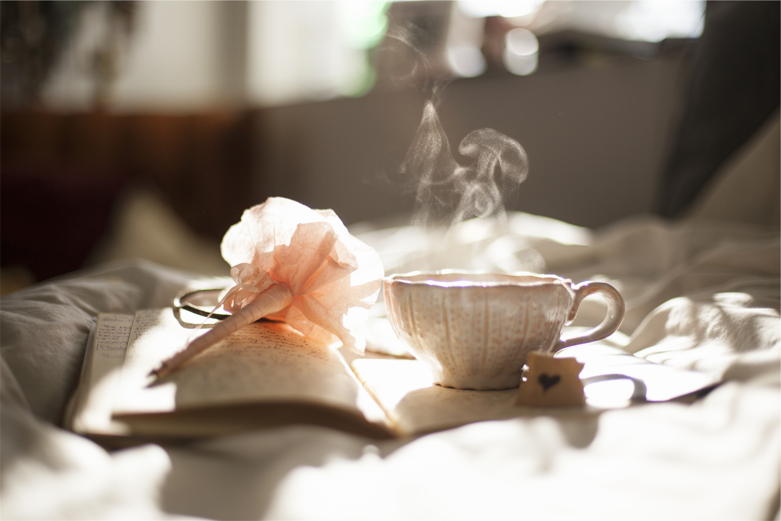 Tea cup with steam and pen on bed